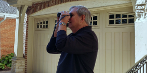 Wayne demonstrates how he uses binoculars to spot things at a distance