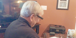 Wayne recently purchased the Orcam MyEye 2.0 for sustained reading. The small, wireless device attaches to the temple of his glasses.