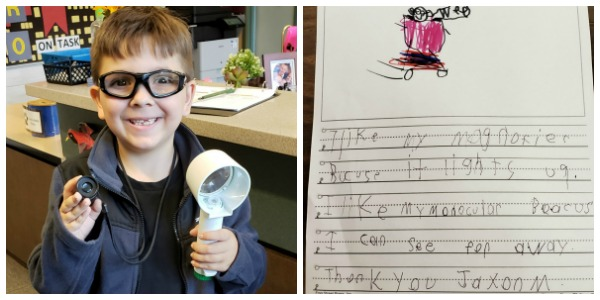 Young child showing off his low vision tools and his thank you note